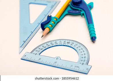 A math concept, close up of blue divider, protractor, and triangle ruler isolated on white