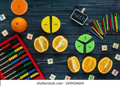 Сolorful math fractions and oranges as a sample on dark wooden background or table. Interesting creative funny math for kids. Education, back to school concept. Geometry and mathematics materials.