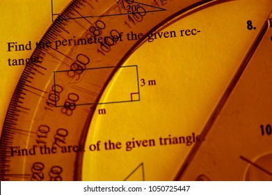 Math still life with protractor and math problems. Clear protractor laying on an open math book. Half moon ruler used in algebra question. Studying math in school.