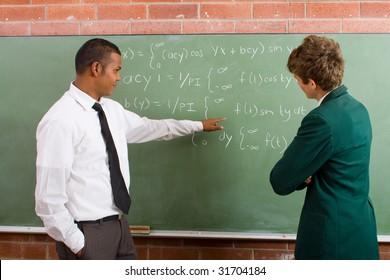 math teacher teaching student in classroom