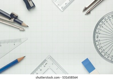 Mathematical instruments surrounding a graph paper creating copy space