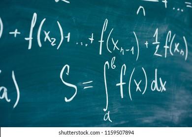 Mathematics function integra formulas written by chalk on the chalkboard.