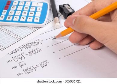 Mathematics, Math Equations close-up. Math homework or math exams. Solving Mathematical Problem with hand holding pencil. Math formula concepts.