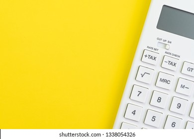 Mathematics, tax calculation, finance or investment concept, white clean calculator on solid yellow background with copy space.