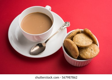Mathri is a Rajasthani/Indian snack and a type of flaky biscuit. Made from flour, water, and cumin seeds. served in a bowl with Hot tea over colourful or wooden background, selective focus