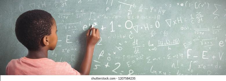 Maths against boy writing with chalk on greenboard in school