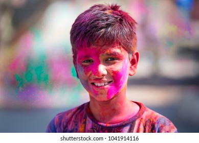 MATHURA - FEB 26: Cheerful teenager boy in colored t-shirt during Color Holi festival in Mathura on 26. 2018 in India