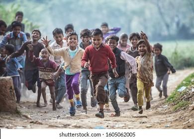 MATHURA, INDIA - Feburary 23,2018: Group of boisterous Indian children running for photograph in Agra, Uttar Pradesh, India.