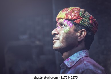 MATHURA, INDIA - Feburary 25,2018: Portrait of Indian man smeared with colours on her face poses for a photograph during the Holi festival celebration in Mathura, India