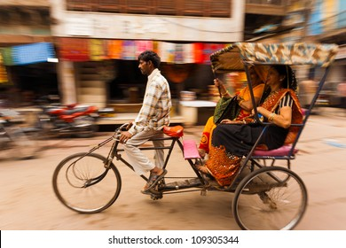 Mathura, India - November 13, 2009: Blurred panning shot of two Indian women laughing while riding a cycle rickshaw, a popular form of taxi, through a busy bazaar