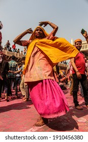 Mathura, Uttar Pradesh, India- January 28 2020: Young indian man dancing with a yellow colored cloth covered in Holi colors, enjoying during the Holi Festival in Mathrua.