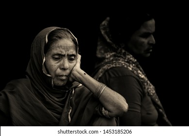 Mathura,India-March 25, 2013: Portrait of a traditionally dressed thoughtful old woman sitting on the bench. Sepia tone photograph.