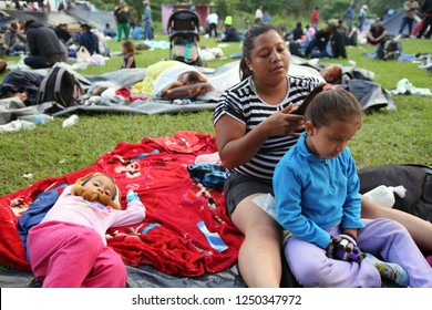 Matias Romero, Oaxaca / Mexico - Nov. 10, 2018: A Salvadoran woman fleeing poverty and gang violence in the third caravan to the U.S. combs her daughter's hair at dawn at an ad hoc migrant shelter.