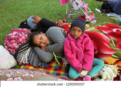 Matias Romero, Oaxaca / Mexico - Nov. 10, 2018: A Salvadoran family fleeing poverty and gang violence in the third caravan to the U.S. wakes up at dawn at an ad hoc migrant shelter at a sports field.