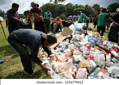 Matias Romero, Oaxaca/Mexico - Nov. 10, 2018: Salvadoran men fleeing poverty and gang violence in the third caravan to the U.S. clean up trash, not all theirs, in a field acting as an ad hoc shelter.