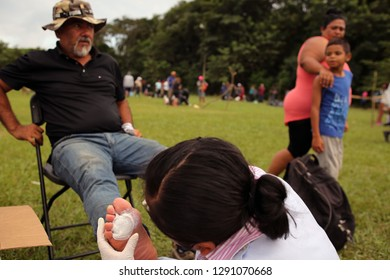 Matias Romero, Oaxaca/Mexico - Nov. 10, 2018: A volunteer nurse treats a blister on the foot of a Salvadoran man fleeing poverty and gang violence in the third caravan to the U.S.