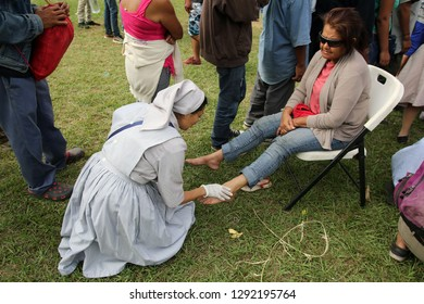 Matias Romero, Oaxaca/Mexico - Nov. 10, 2018: A volunteer nurse examines the foot of a Salvadoran woman fleeing poverty and gang violence in the third caravan to the U.S.