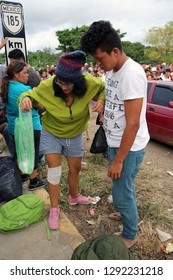 Matias Romero, Oaxaca/Mexico - Nov. 10, 2018: A young Salvadoran man and his injured mother fleeing poverty and gang violence in the third caravan to the U.S. move roadside to wait for a truck.