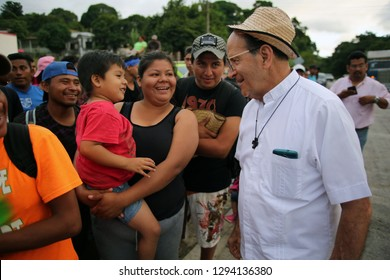 Matias Romero, Oaxaca/Mexico - Nov. 10, 2018: The local Catholic priest who arranged trucks for Salvadorans fleeing poverty and gang violence in the third caravan to the U.S. jokes with a child.