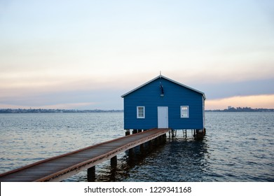 The Matilda Bay or Crawley Edge boatshed, Perth, Western Australia. Iconic blue boathouse stands above the waterline at sunset