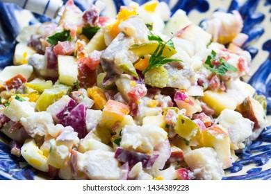 Matjes mit Apfel, Gurke, Zwiebeln und Eiern als Salat angemacht in einer blauen Schüssel