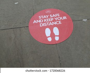 MATLOCK, UNITED KINGDOM, 1st May, 2020: A social distancing reminder sign on the ground outside a post office saying stay safe and keep your distance
