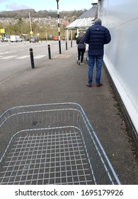 MATLOCK, UNITED KINGDOM, 4th April, 2020: Shoppers queuing outside a supermarket with trolleys standing two metres apart and observing social distancing measures to stop the spread of disease