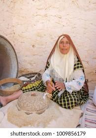 MATMATA, TUNISIA - August 30, 2010: Berber woman in traditional clothes in her house - troglodyte dwellings - in Matmata. Sahara Desert, Tunisia, Africa.