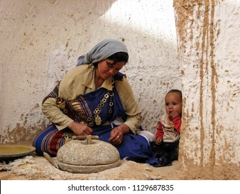 MATMATA, TUNISIA-OCT.  21, 2009: In a rural area outside Matmata, a Tunisian woman grinds grain outside her cave dwelling using a traditional mortar with her young son looking on.