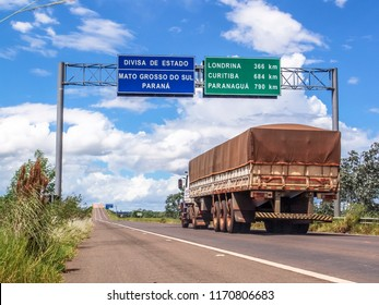 Mato Grosso do Sul, Brazil, March ,9, 2006. Truck on the road crosses the border between the states of Mato Grosso do Sul and Parana, with signs indicating distances in kilometers to the cities.