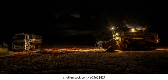 MATO GROSSO DO SUL, BRAZIL - FEBRUARY 28, 2017: New Holland TC57 tractor parked on the side of a truck with lights turned on. Night scene after the soybean harvest season on farm.