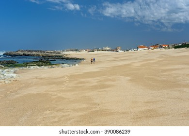 Matosinhos, Portugal - April 21, 2015: beautiful empty rocky beach in northern Portugal  on a beautiful spring day seeing a loving couple walking