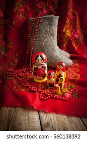 matryoshka, boots, and beads against a red kerchief