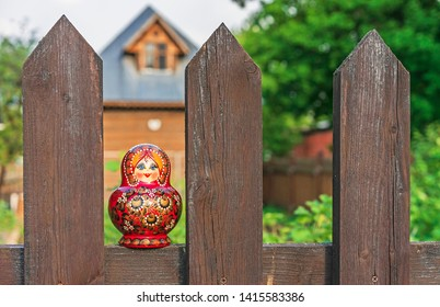 Matryoshka doll on a wooden fence in the village. Matryoshka is a national Russian souvenir.