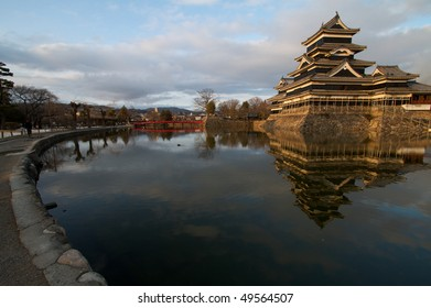 Matsumoto Castle with foreground showing reflection of castle, sky and bridge in the water