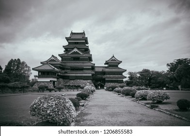 Matsumoto Castle Japan premier historic castle - Black crow castle - Nagano, Japan on cloudy day in summer with grass lawn flower bushes black and white image