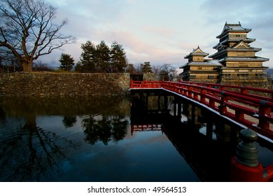 Matsumoto Castle with reflection of red bridge and trees on the water