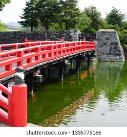 Matsumoto, Nagano Prefecture/Japan-April 2016:  Vermillion bridge spanning the moat to the Matsumoto 'Crow' Castle grounds.