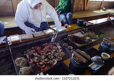 Matsusaka, Japan - Mar 18, 2018. Woman serving seafood at a traditional restaurant near Ise Bay in Matsusaka, Japan.
