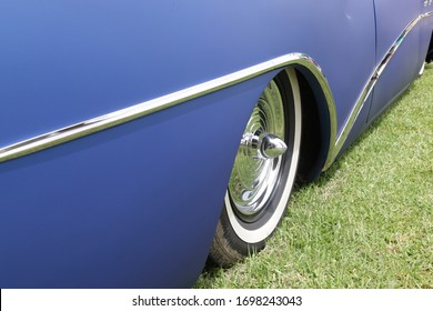 Matt blue Buick rear wheel and quarter panel with lots of chrome.