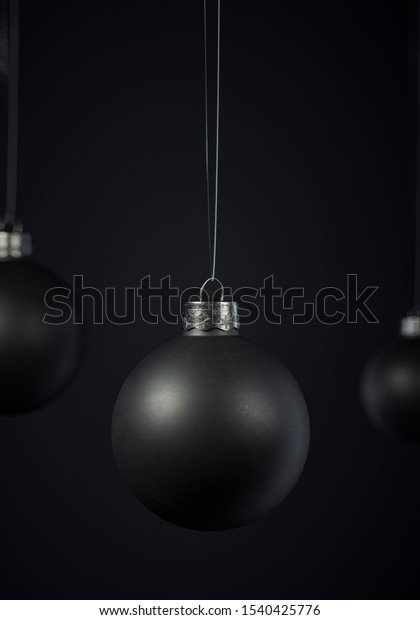 Matte black Christmas balls hanging centered on a black background for seasonal Holiday celebrations and themes