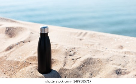 Matte black steel thermo bottle for water in sand of the beach on background of sea. Empty blank for mockup. Say no to plastic.
