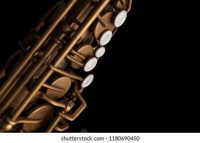 Matte finish saxophone with pearl keys on black background