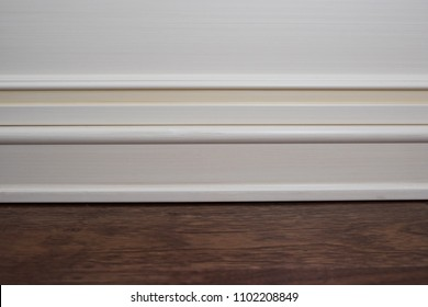 Matte wall, white baseboard and tiles immitating hardwood flooring