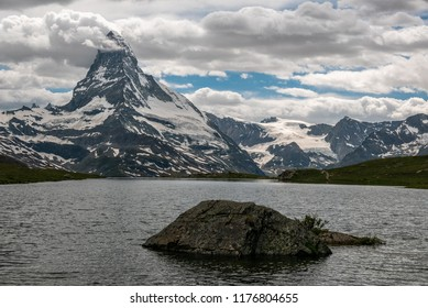 Matterhorn (Monte Cervino, Mont Cervin) pyramid and Stellisee lake in a cloudy day.