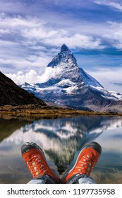 Matterhorn peak with hiking boots in Swiss Alps.