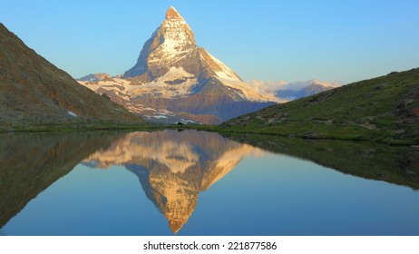 Matterhorn peak and peaceful reflection on Riffelsee at early morning