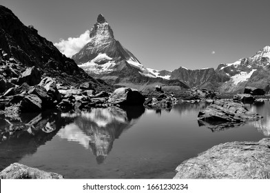 "Matterhorn world famous iconic peak near Zermatt in Wallis Switzerland on the swiss-italian border in the Alps. Beautiful reflection in the ""Riffelsee"" at Gornergrat Railway track, black and white"