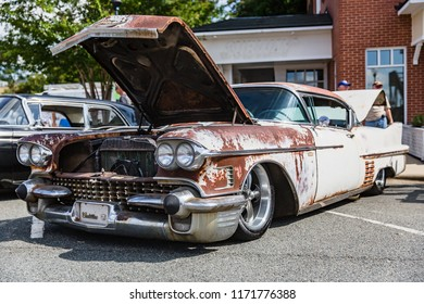 MATTHEWS, NORTH CAROLINA - SEPTEMBER 3 2018: Onlookers inspect a rusty classic Cadillac parked on display at the Matthews Auto Reunion