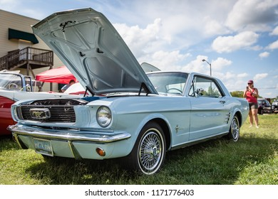 MATTHEWS, NORTH CAROLINA - SEPTEMBER 3 2018: A woman photographs a restored vintage Ford Mustang at the Matthews Auto Reunion